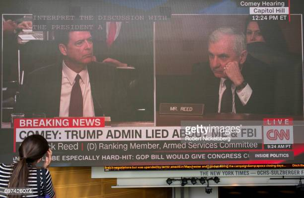 On a large television screen former FBI Director James Comey left answers questions posed by US Senator Jack Reed Rhode Island right during Comey's...