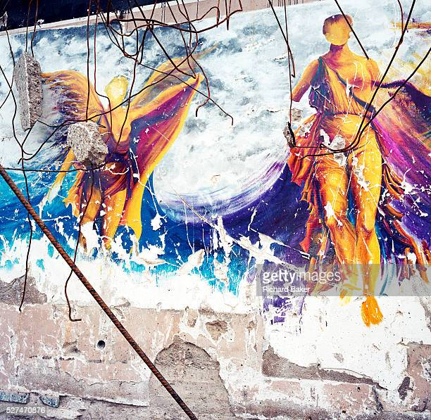 On a partiallydemolished building a mural of the ancient Goddess Nike remains chipped and scraped on an old restaurant wall Nike was the Goddess of...