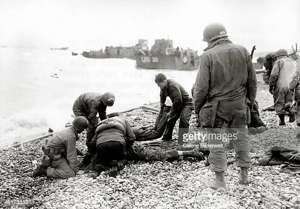 On a pebble beach at Omaha Beach US soldiers deal with injuries6th June 1944 All these men are Engineers 5th or 6th Engineer Special Brigade The...