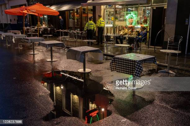 On a rainy night in Soho, Met police officers make a presence outside Bar Italia on Frith Street at a time when recently re-opened bars and...