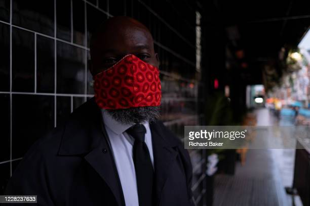 On a rainy night in Soho, security man 'H' wears a bright red facial covering outside a business at a time when recently re-opened bars and...