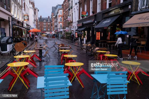 On a rainy night in Soho, tables set up for social distancing on Frith Street remain vacant at a time when recently re-opened bars and restaurants...