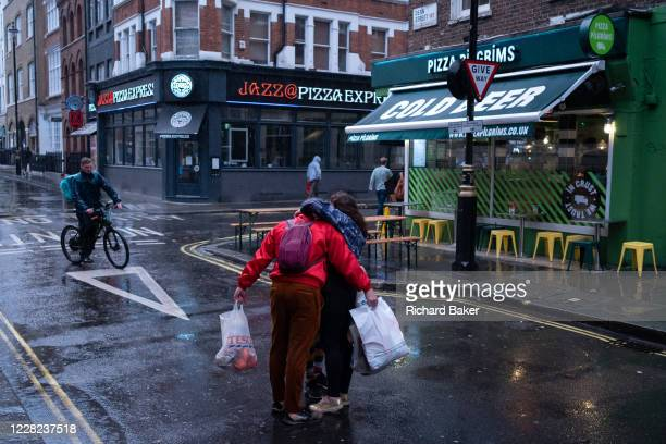 On a rainy night in Soho, three friends hug on Dean Street during the coronavirus pandemic, on 27th August 2020, in London, England.