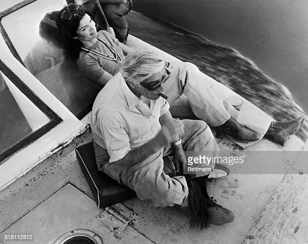 On a river trip down the Nile Jacqueline Onassis relaxes and stretches out while her husband Aristotle sits on a cushion and enjoys a cigar