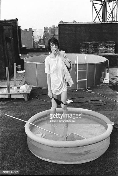 On a SoHo rooftop American poet and musician Patti Smith stands in a wading pool and mimes with her underwear around her knees New York New York July...
