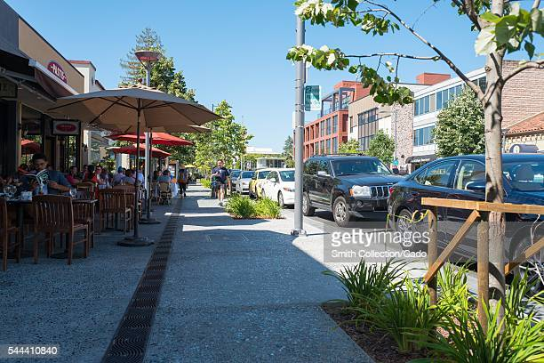 On a sunny day in Palo Alto diners eat outdoors at restaurants along California Street while people stroll past Palto Alto California 2016