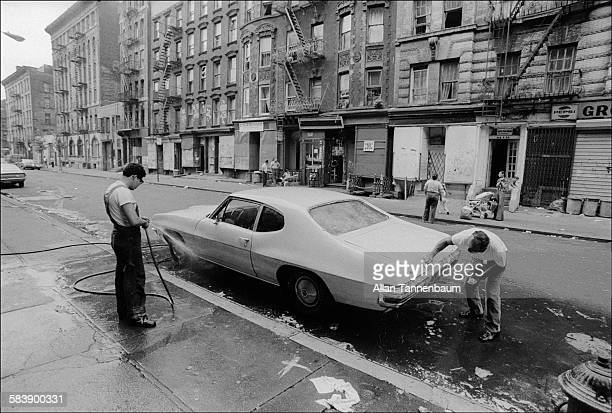 On a the Lower East Side street a pair of men wash a car in front of boardedup storefronts New York New York September 9 1974