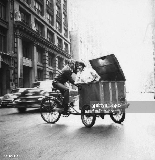 On a tricycle, American photographer William 'Bill' Helburn peddles Italian actress and model Elsa Martinelli , who rides in an attached cart, across...