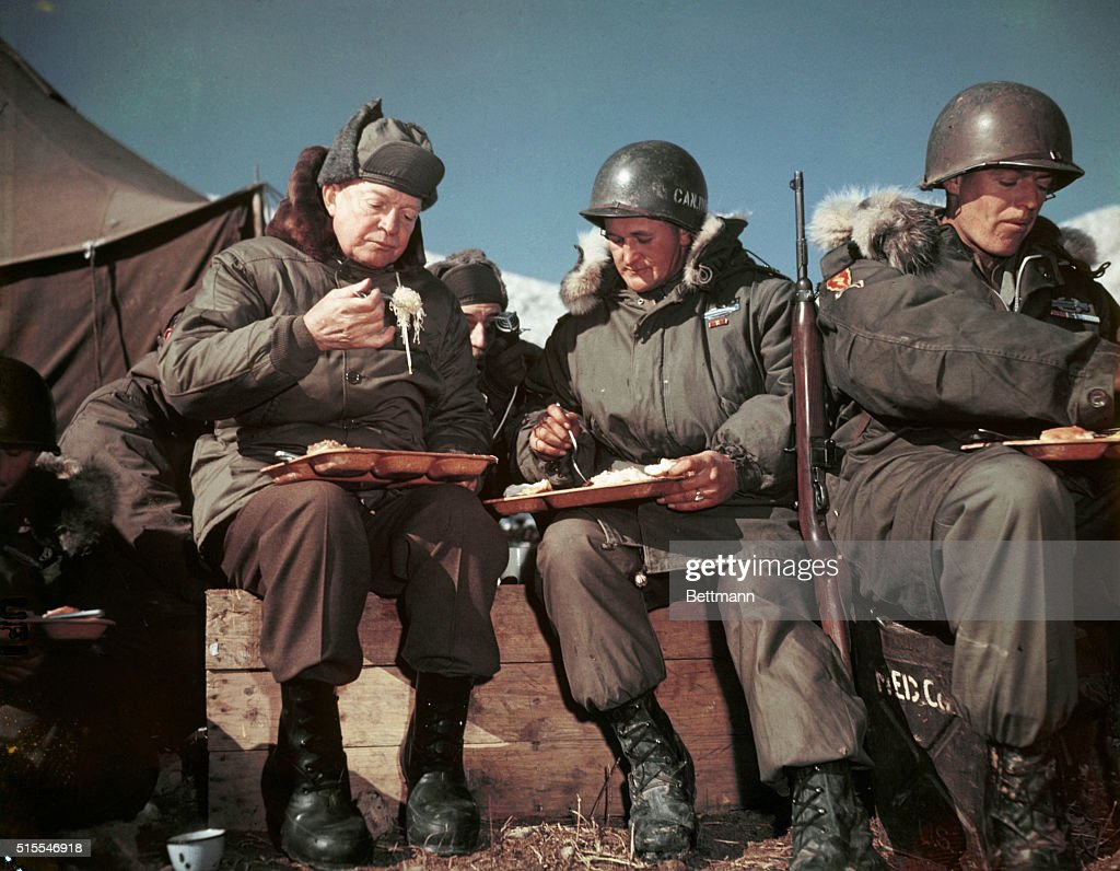 On a visit to the front lines, President Eisenhower eats with American soldiers