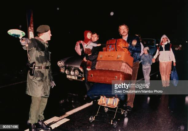 On a wet snowy night a West German border guard directs East German refugees one of whom pushes a stack of suitcases on a baby stroller as they cross...