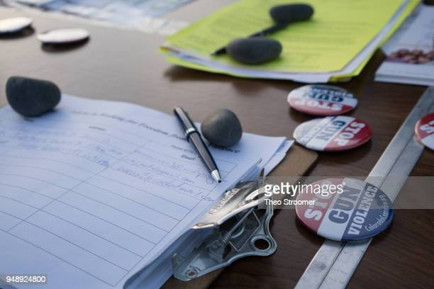 On a windy day rocks are used to hold down signup sheets during the Vote For Our Lives rally and vigil at Columbine High School on April 19 2018 in...