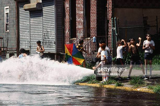 On an unidentified Brooklyn street a group of children play in the water from an opened fire hydrant in the wake of the New York City blackout...