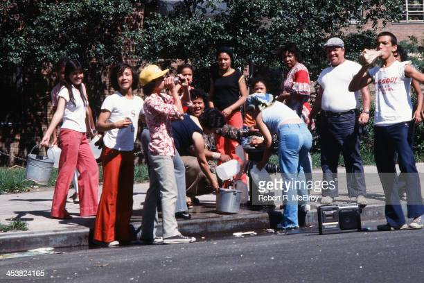 On an unidentified Brooklyn street people fill up buckets and bottles from an opened fire hydrant in the wake of the New York City blackout Brooklyn...