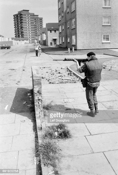 On an unidentified street a British Soldier aims his rifle across the road during a patrol Belfast Northern Ireland August 1972 In the distance two...