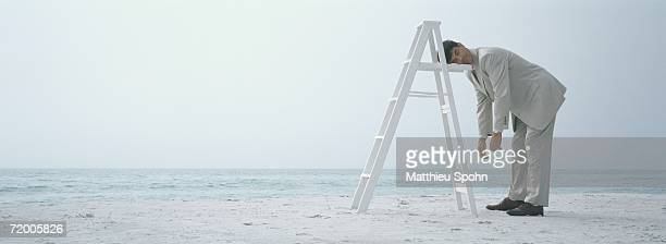 On beach, businessman sleeping standing up, resting head on ladder