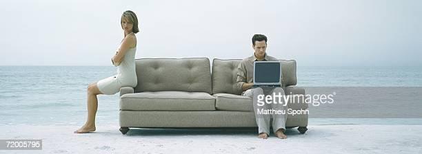 On beach, couple sitting apart on sofa