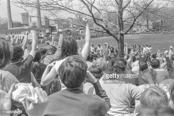 On Blanket Hill, Kent State University students raise their fists as faculty use megaphones to try and convince the antiwar demonstrators and...