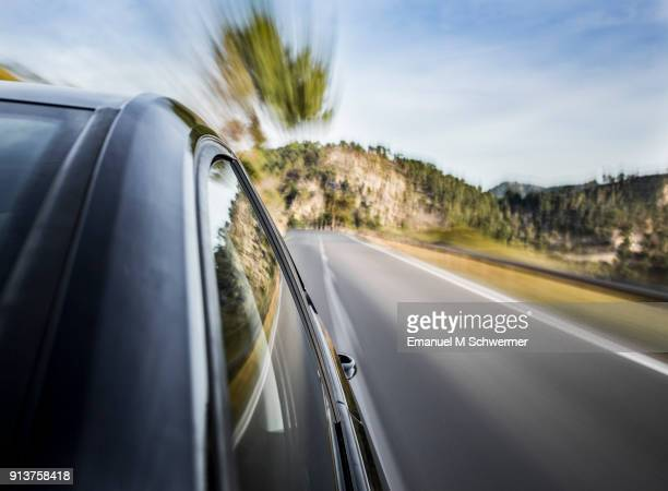 on board a black german car, shot with a mounted / rigged camera, long-exposure shot with the a-pillar in foreground, reflections in the surface of the car, streaking lights and motion blurred background. - umweltfahrzeug stock-fotos und bilder