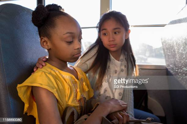 on bus, young girl consoles her sad friend - bullying stock pictures, royalty-free photos & images