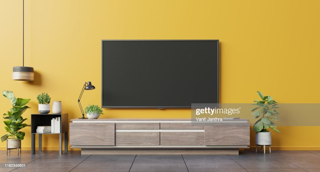 TV on cabinet in modern living room on yellow wall background. : Stock Photo