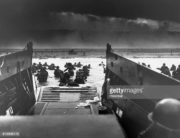 On DDay June 6 a landing craft just vacated by invasion troops points towards a fortified beach on the Normandy Coast American soldiers wade to shore...