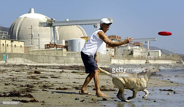 On dogpatch beach just North of San Onofre Nuclear Power Plant, Michael Virden flips the frisbee, into the surf, for Mombo, his daughter's yellow...