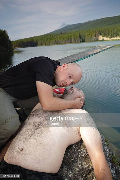 cpr on drowning victim beside mountain lake - drowning victim photos stock photos and pictures