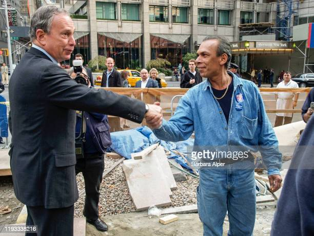 On election day, American politician New York City Mayor Michael Bloomberg shakes hands with a construction worker, on 7th Avenue near West 53rd...