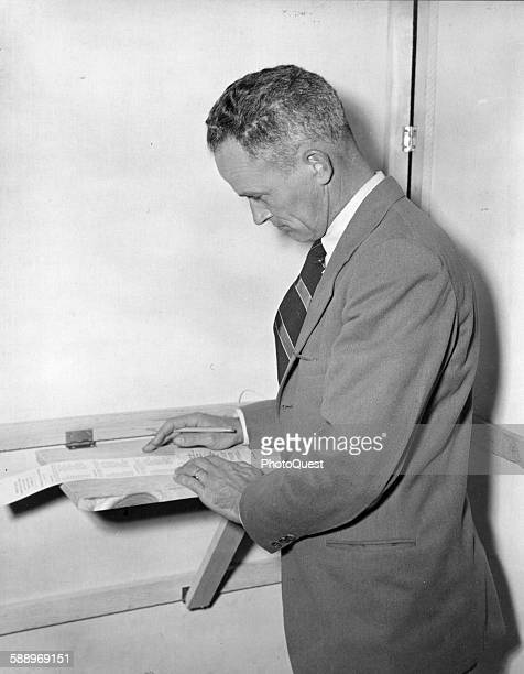 On Election Day Bennett W King studies his ballot in the voting booth Fairfax Virginia November 2 1948