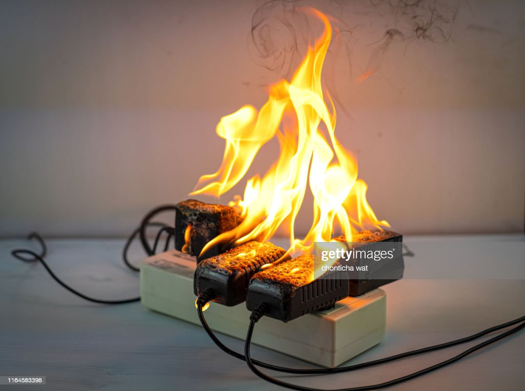 On fire adapter at plug Receptacle on white background, Electric short circuit failure resulting in electricity wire burnt : Stock Photo