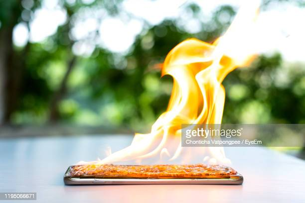 on fire smart phone screen is cracked with blurred background - burning stock pictures, royalty-free photos & images