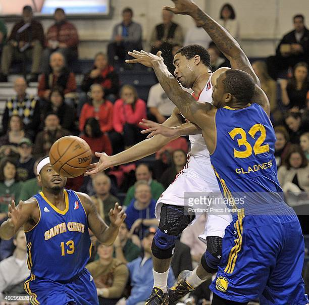On Friday, January 25 Maine, Andre Barrett passes off to a teammate after getting trapped by Santa Cruz, Mickell Gladness and, Stefhon Hannah...