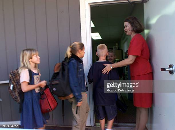 On her first day at the Little Red School House superintendent principal and teacher Jan Lee ushers students into a classroom Tuesday morning