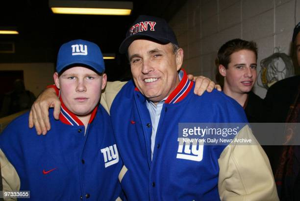 On his last weekend in office Mayor Giuliani leaves Veterans Stadium with his son Andrew after taking in a football game between the New York Giants...