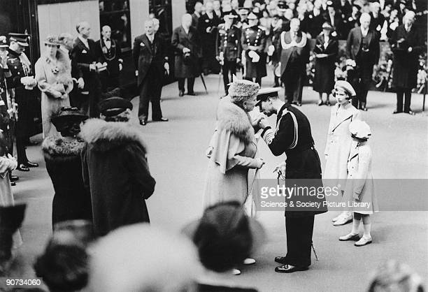 On his return from his North American tour King George kisses the hand of his mother Queen Mary at Waterloo Station His daughters Princess Elizabeth...