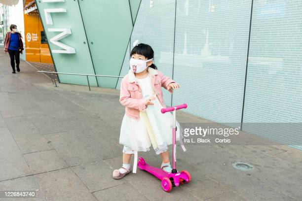 On Memorial Day weekend a young girl wears a mask with a tongue sticking out rides on her scooter by Lincoln Center On May 24 New York State Governor...