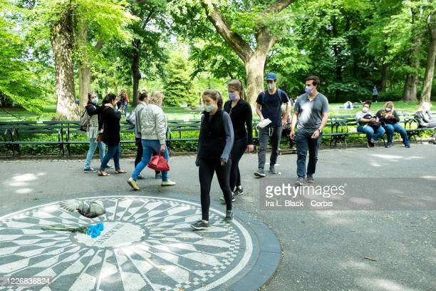 On Memorial Day weekend crowds of people wearing masks walk past a bouquet of flowers that lay at the Imagine mosaic in Strawberry Fields as a...