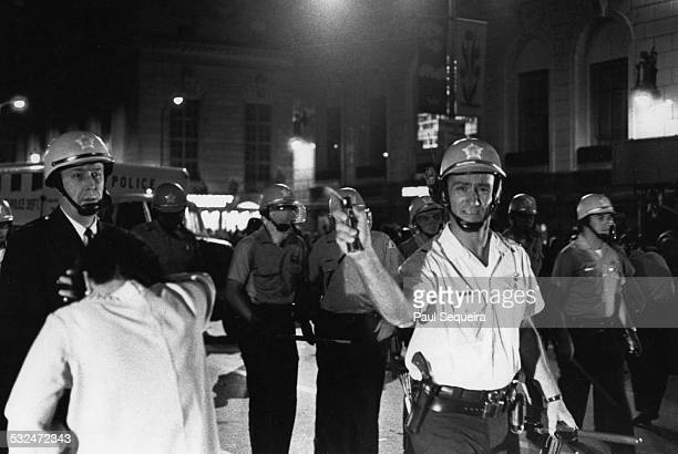 On Michigan Avenue a Chicago police lieutenant sprays mace and hits a female shopper as he pursues a newspaper photographer during protests at the...