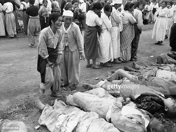 On October 19 Korean women from Hamhung identify the bodies of some 300 political prisoners who were killed by the North Korean Army by being forced...