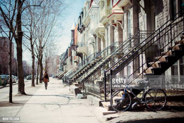 On person walking on a sidewalk in the street of Montreal with outdoors stairs and a bicycle