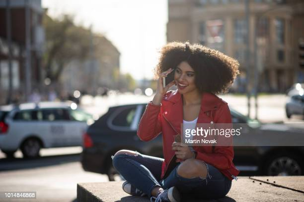 On phone - young black woman having call in street