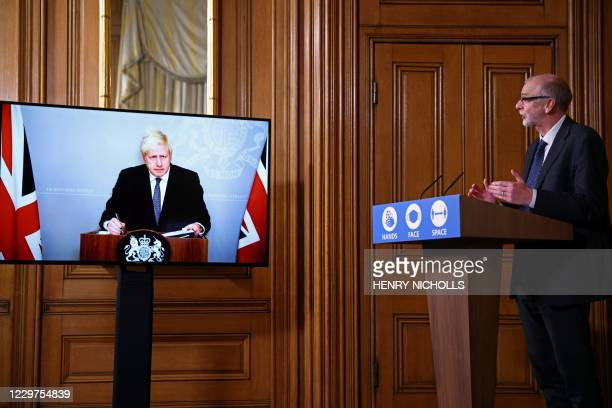 On screen due to selfisolating Britain's Prime Minister Boris Johnson and Director of the Oxford Vaccine Group Andrew Pollard hold a virtual press...