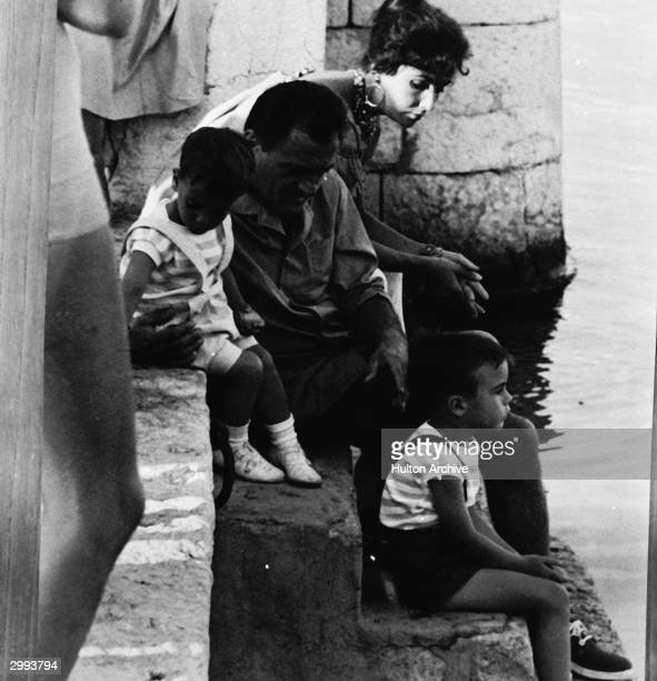 On some steps leading down to water Britishborn actor Elizabeth Taylor sits with her family husband film producer Mike Todd and sons Christopher L...