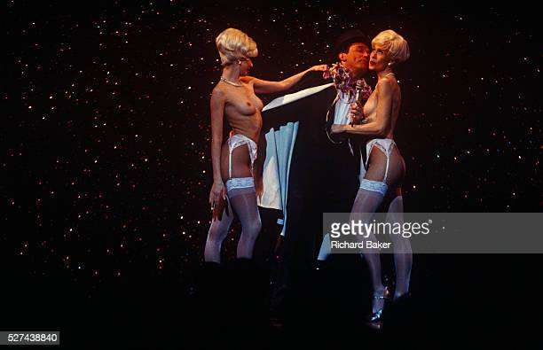 On stage two beautiful topless girls stand seminaked with a gentleman admirer during a variety show at the famous Parisian cabaret company Paradis...