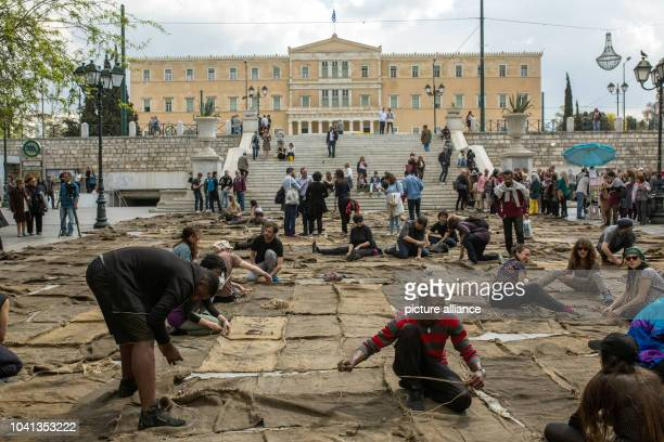 On Syntagma Square young people sew together jute sacks with rough thread as part of a performance 'Check Point Prosfygika' by the Ghanaian artist...