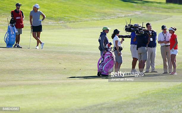 On the 18th fairway a USGA rules offical informs Brittany Lang that Anna Nordqvist was assessed a two stroke penalty for grounding her club in the...