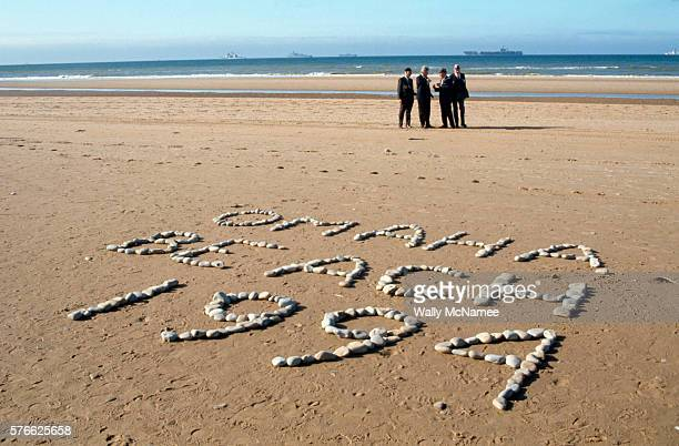 On the 50th anniversary of DDay President Bill Clinton standing near a sign made out of stones reading 'Omaha Beach 1994' talks with war veterans who...