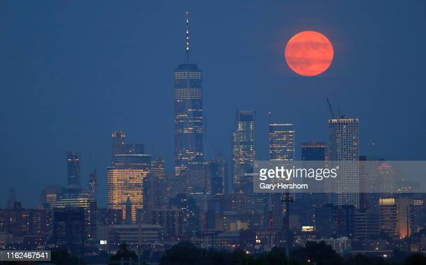 On the 50th anniversary of the launch of Apollo 11 the full buck moon rises above the skyline of lower Manhattan and One World Trade Center in New...