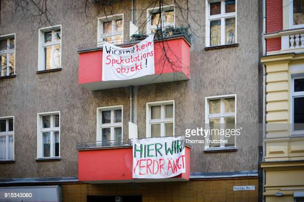 On the balconies of a residential building in Berlin Neukoelln hang banners with the inscription 'here is displaced' and 'We are not a speculative...