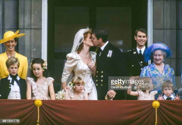 On the balcony of Buckingham Palace Sarah Duchess of York and Prince Andrew Duke of York kiss each other after their wedding London England July 23...